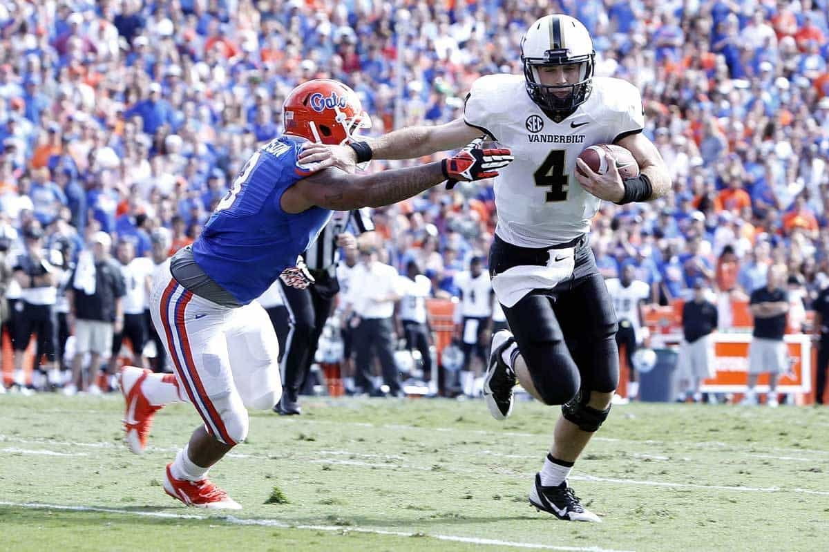 Nov 9, 2013; Gainesville, FL, USA; Vanderbilt Commodores quarterback Patton Robinette (4) runs the ball in for a touchdown as he stiff arms Florida Gators linebacker Antonio Morrison (3) during the second quarter at Ben Hill Griffin Stadium. Photo: Kim Klement-USA TODAY Sports