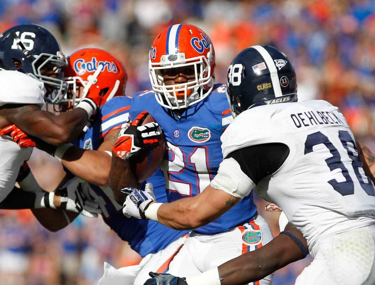 Nov 23, 2013; Gainesville, FL, USA; Florida Gators running back Kelvin Taylor (21) runs with the ball as Georgia Southern Eagles linebacker Kyle Oehlbeck (38) defends during the first quarter at Ben Hill Griffin Stadium. Photo: Kim Klement-USA TODAY Sports