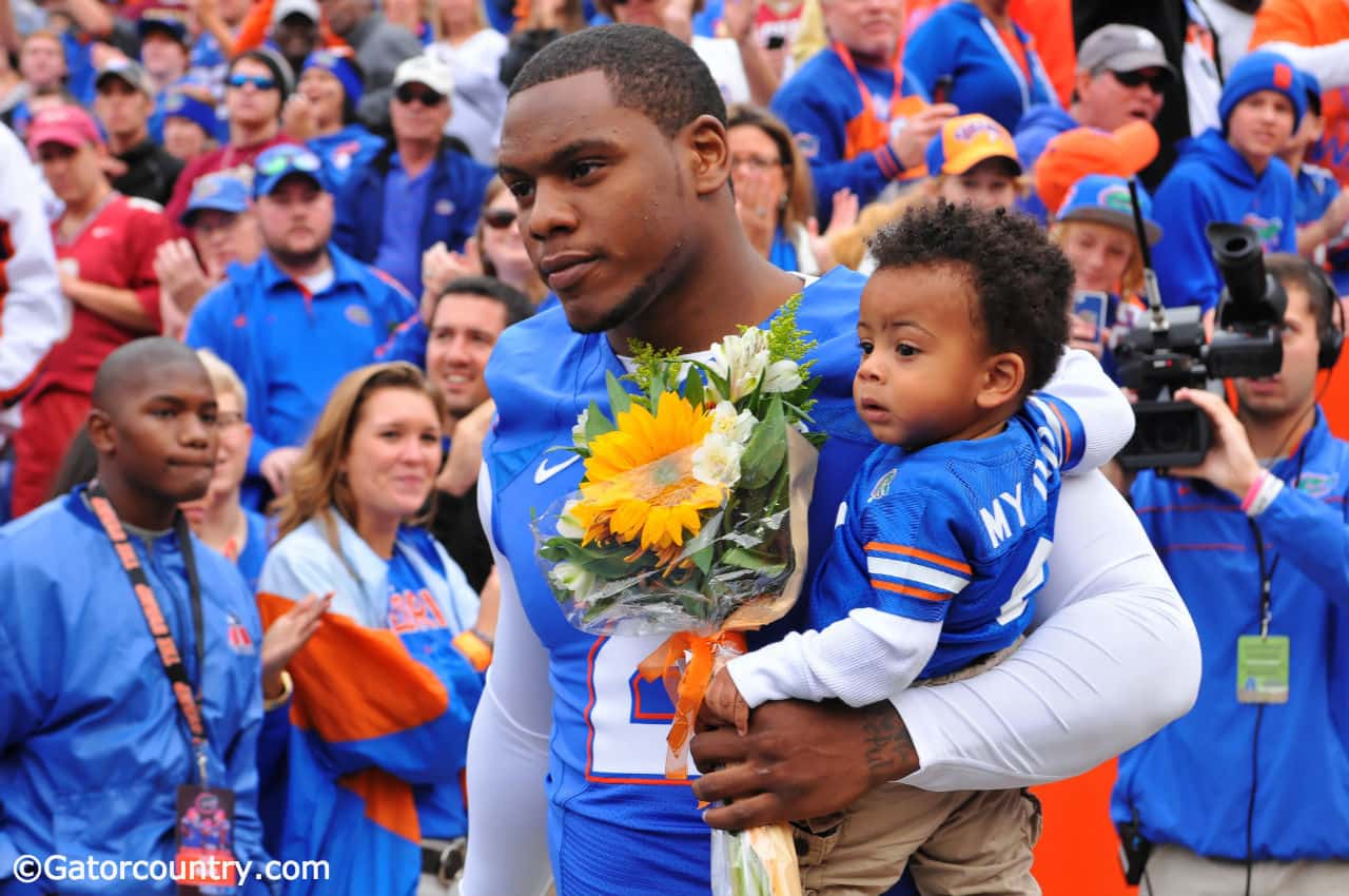 Dominique Easley walks out with his son during Florida's senior day ceremony.