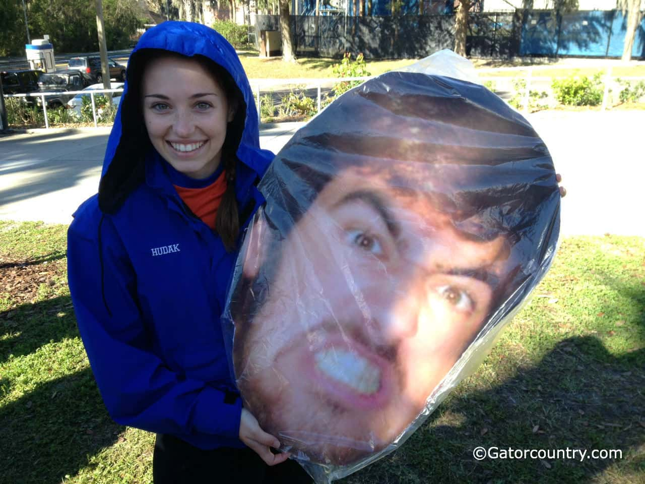 Florida rowing team member Lauren Hudak holds up a big head of her coach.