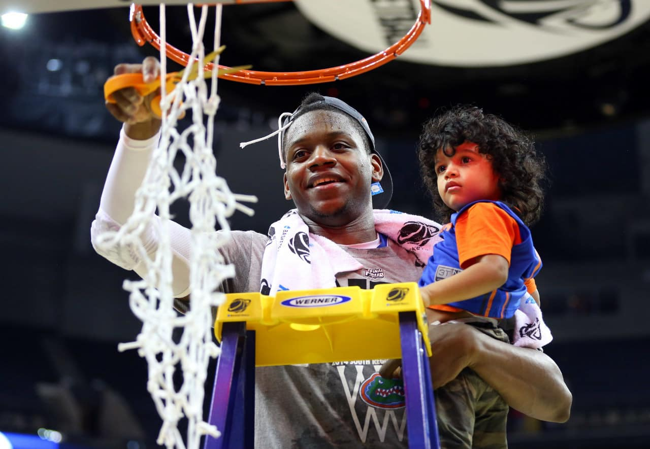 Mar 29, 2014; Memphis, TN, USA; Florida Gators forward Will Yeguete (15) cuts down the net with Braxton Bruno, son of assistant coach Rashon Bruno (not pictured) after defeating the Dayton Flyers in the finals of the south regional of the 2014 NCAA Mens Basketball Championship tournament at FedEx Forum. Florida won 62-52. Photo by: Spruce Derden-USA TODAY Sports