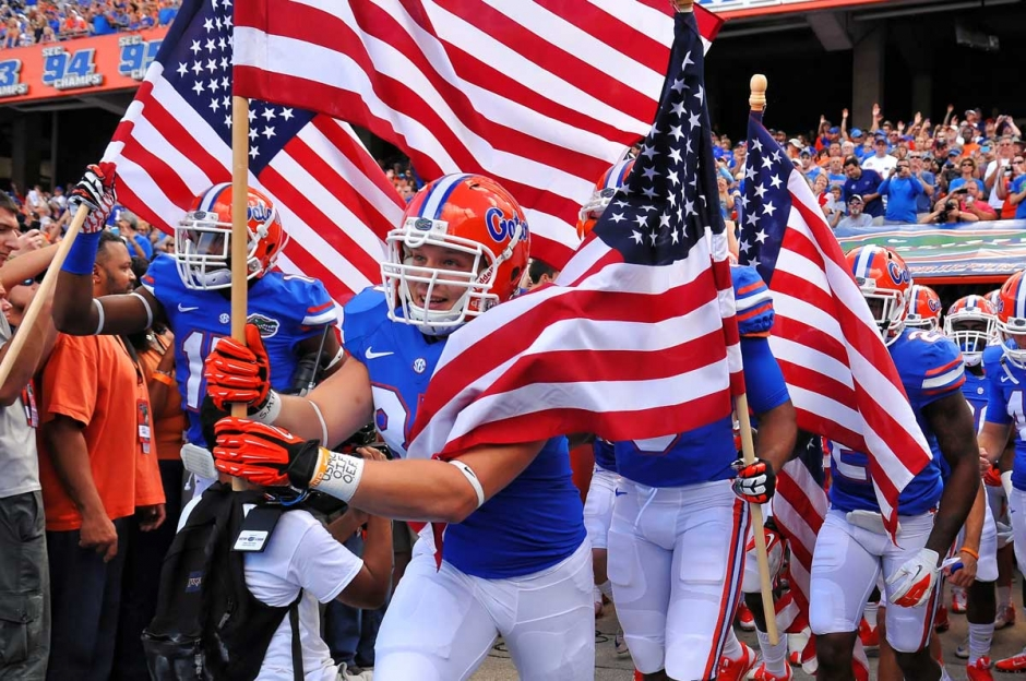 Florida Gators running on field during pre-game in The Swamp, carrying American flags 11-23-2013