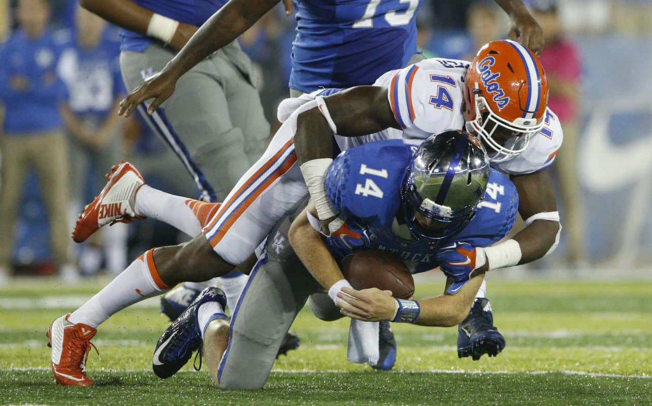 Sep 19, 2015; Lexington, KY, USA; Florida Gators defensive lineman Alex McCalister (14) tackles Kentucky Wildcats quarterback Patrick Towles (14) during the game at Commonwealth Stadium. Florida defeated Kentucky 14-9. Mandatory Credit: Mark Zerof-USA TODAY Sports