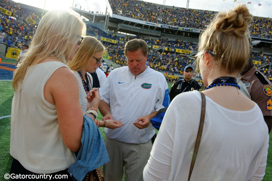 Florida Gators head coach Jim McElwain gives out gum to his daughters, a post game ritual for the family, after losing to the University of Michigan Wolverines - Florida Gators football- 1280x852