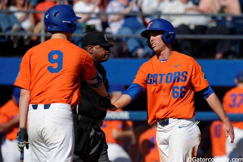 University of Florida senior Ryan Larson celebrates with Christian Hicks after scoring to give UF a 5-2 lead over Miami- Florida Gators baseball- 1280x852