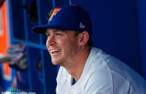 University of Florida infielder Deacon Liput sits in the dugout as the Florida Gators warm up before their season opener against Siena- Florida Gators baseball- 1280x853