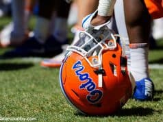 A player rests on his helmet while Dan Mullen addresses the Florida Gators football team after a spring practice- Florida Gators football- 1280x853