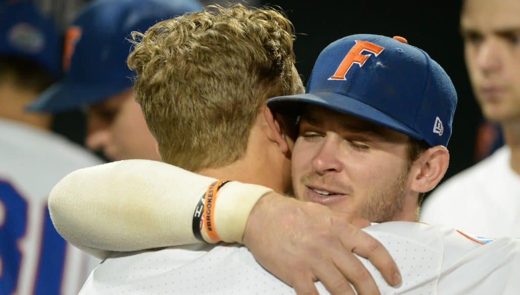 Jun 22, 2018; Omaha, NE, USA; Florida Gators second baseman Blake Reese (12) and shortstop Deacon Liput (8) hug after the loss against the Arkansas Razorbacks in the College World Series at TD Ameritrade Park. Mandatory Credit: Steven Branscombe-USA TODAY Sports