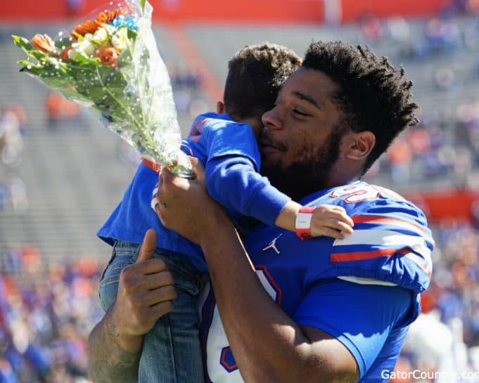 Florida Gators defensive lineman Cece Jefferson holds his son during senior day- 1280x1024