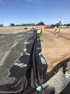 Workers dig trenches to add an irrigation system under the field Florida Gators new baseball stadium- Florida Gators baseball- 1280x1707